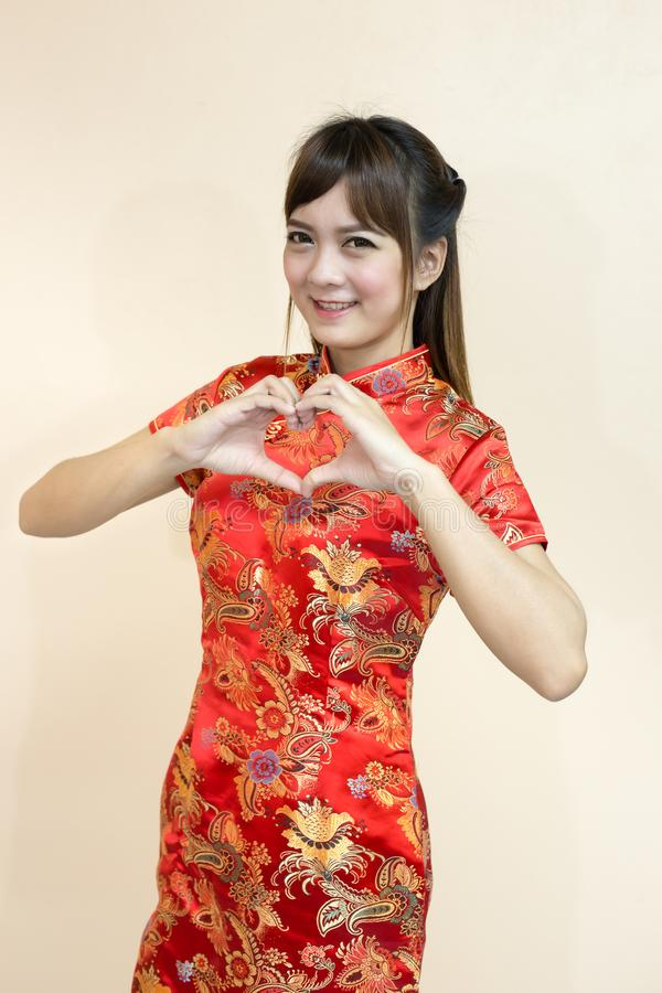 用繁体中文或cheongsam的亚洲妇女问候与手推力欢迎表示和幸运和指点在池氏 免版税库存照片