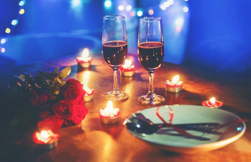 用红心在板材和夫妇香槟的叉子匙子装饰的华伦泰晚餐浪漫爱概念浪漫桌设置 库存图片