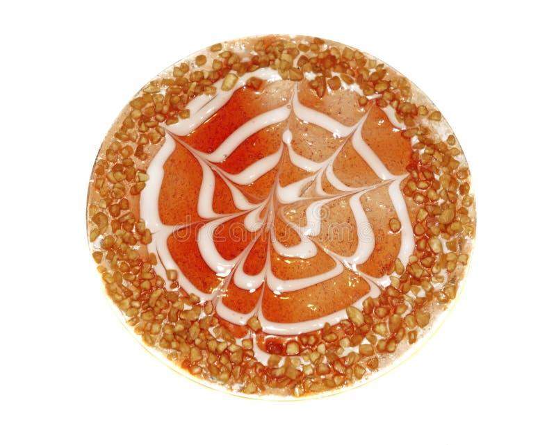 用红色莓果果冻和被击碎的坚果装饰的蛋糕被隔绝 免版税库存图片