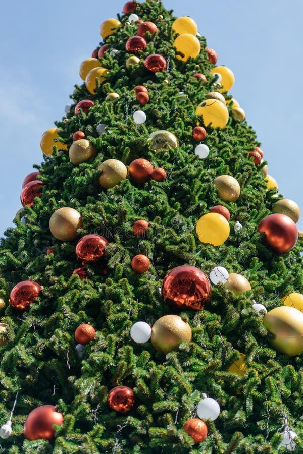 用红色,黄色和银色装饰品装饰的圣诞树有明亮的天空背景 免版税图库摄影
