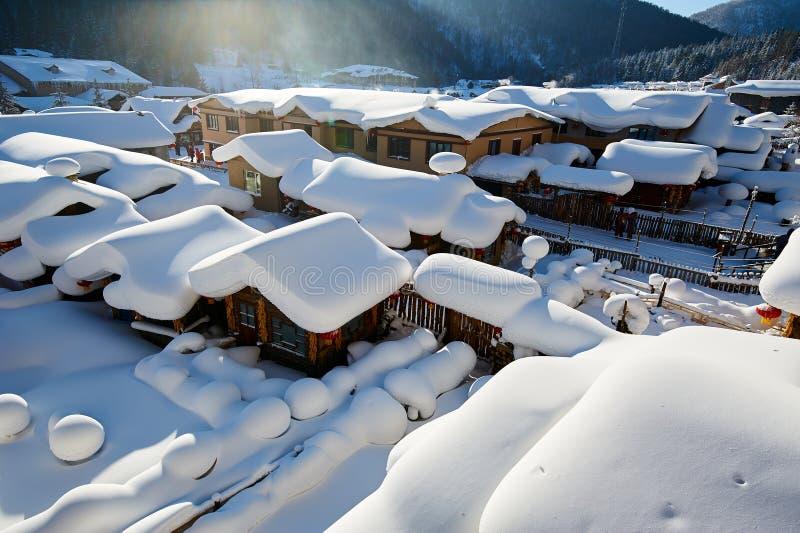 用纯净的白色雪盖的村庄房子 免版税库存照片