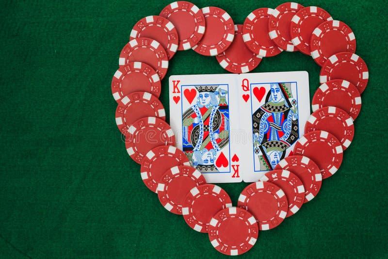 用纸牌筹码做的心脏,与心脏的国王和女王/王后,在一张绿色背景桌 与拷贝空间的顶视图 免版税库存图片