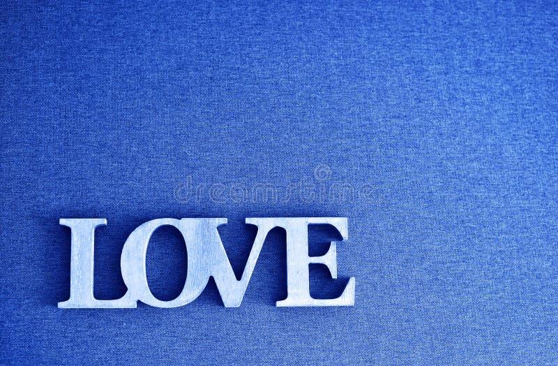 用经典蓝2020颜色在灰色画布纹理背景上书写LOVE字的木字 2020年颜色 库存图片