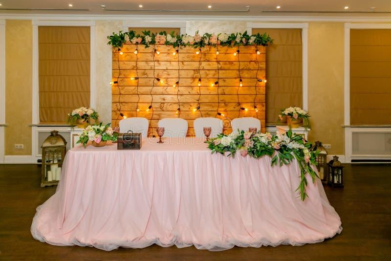 用绿叶和长的布料装饰的新婚佳偶的美丽的白色饭桌 在桌,a上的一长的插花 库存图片