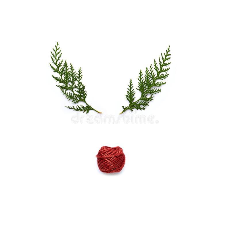 用绿色枝杈和红色麻线做的符号驯鹿面孔 免版税库存图片