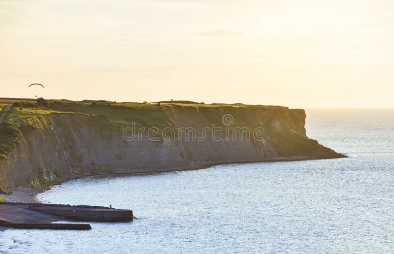 用绿草盖的岩石峭壁在日落 在他们的人实践的滑翔伞 E 库存图片