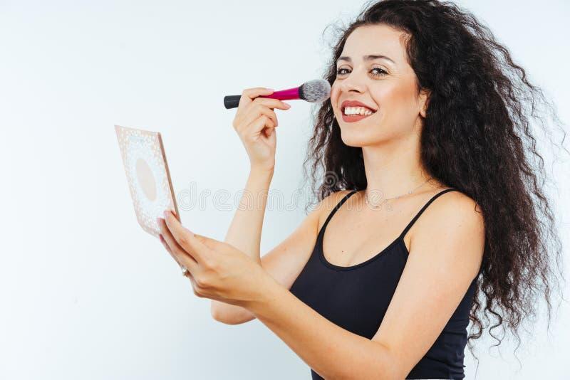 用美容产品制作卷发的年轻美模 免版税库存图片