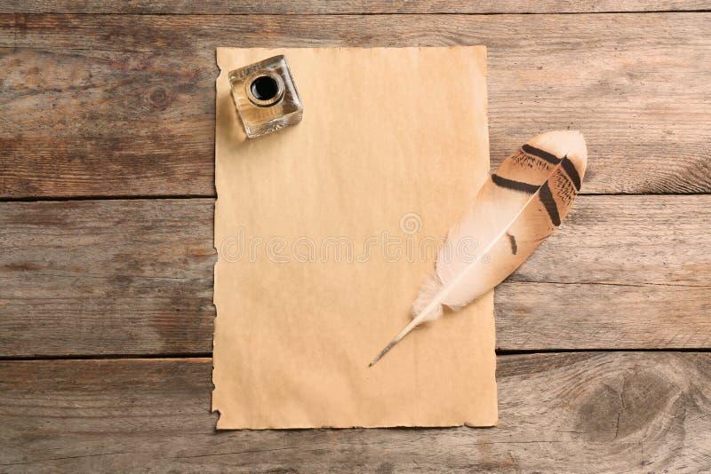 用羽毛装饰笔、墨水池和空白的羊皮纸在木桌,顶视图上 免版税库存照片