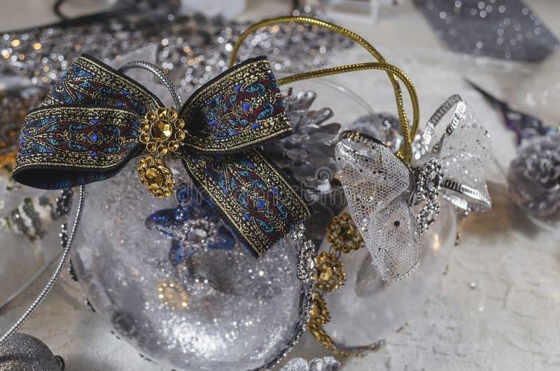 用耶稣和金黄弓诞生充满的雪和透明圣诞节球  免版税库存照片
