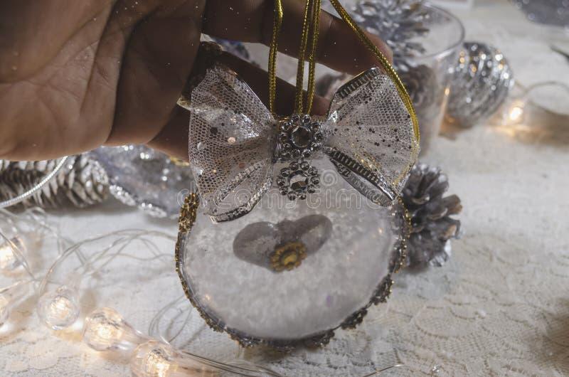 用耶稣和金黄弓诞生充满的雪和透明圣诞节球  库存照片