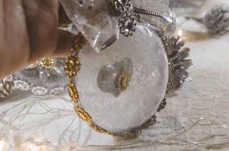 用耶稣和金黄弓诞生充满的雪和透明圣诞节球  免版税库存图片