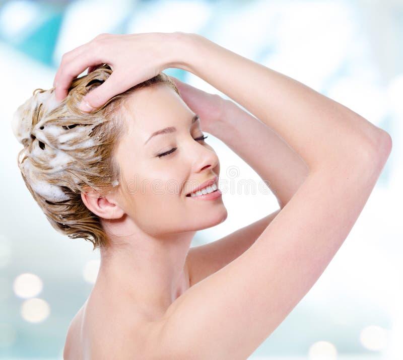 用肥皂擦洗她的头发的微笑的妇女 库存图片