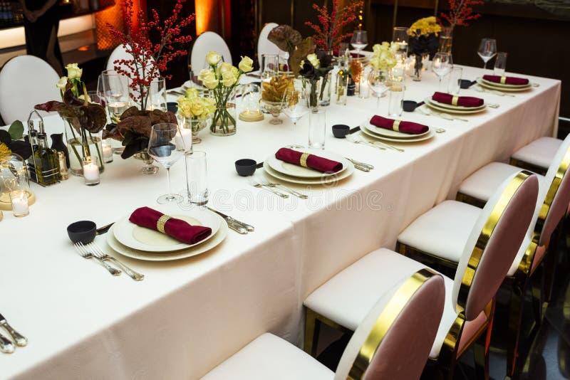 用花和布料餐巾装饰的一张装饰的桌 库存照片