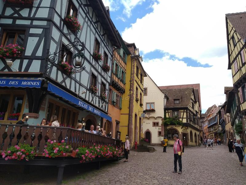 用花和房子装饰的舒适餐馆有五颜六色的门面的在里屈埃维街道  库存照片