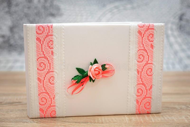 用花和桃红色鞋带装饰的婚姻的愿望书 库存照片