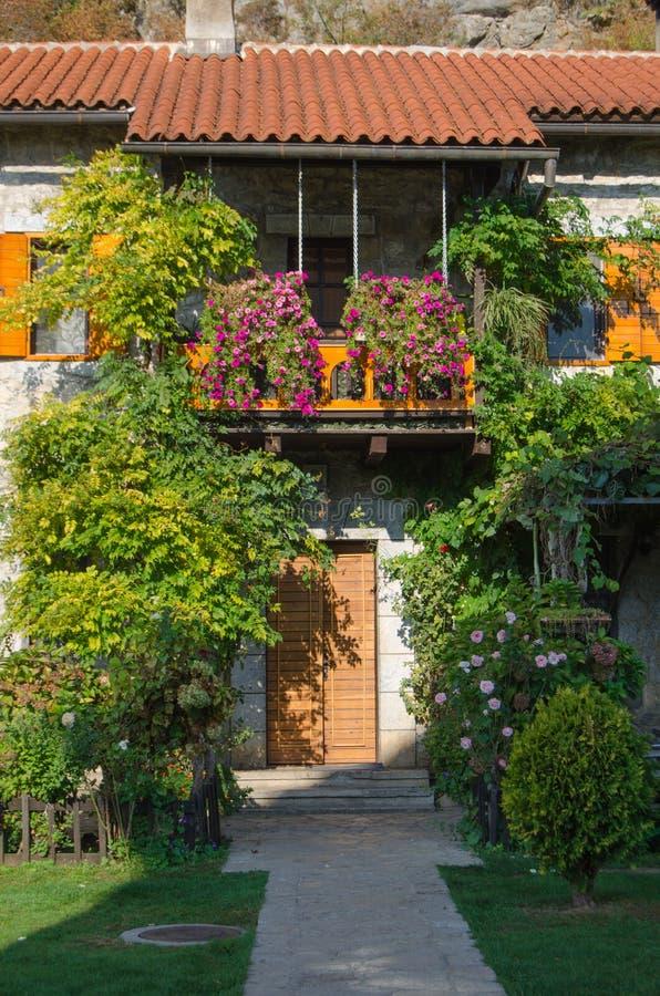 用花和绿叶、老修道院门面和阳台有红瓦顶的装饰在夏天 免版税库存照片