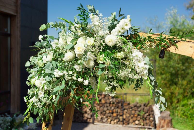 用花和绿叶装饰的一部分的美丽的圆的婚礼曲拱在湖或河附近户外,元素 免版税图库摄影