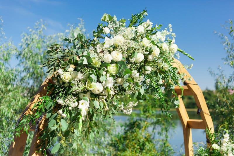 用花和绿叶装饰的一部分的美丽的圆的婚礼曲拱在湖或河附近户外,元素 库存照片