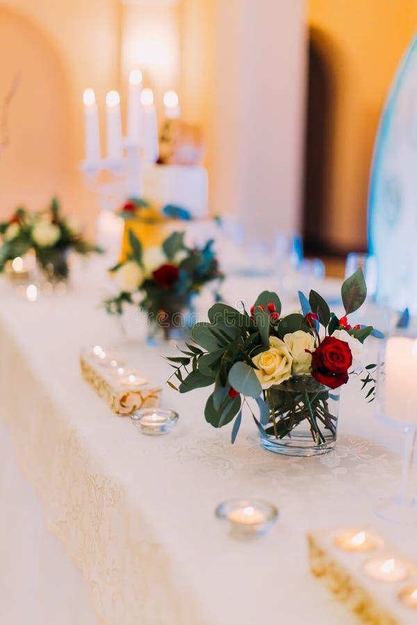 用花和蜡烛装饰的白色婚礼桌准备好客人 杏仁庆祝红色某个婚礼 免版税库存图片
