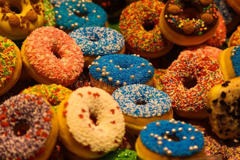 用花梢碎屑装饰的五颜六色的油炸圈饼的陈列在鹿特丹,荷兰市场大厅里  免版税图库摄影