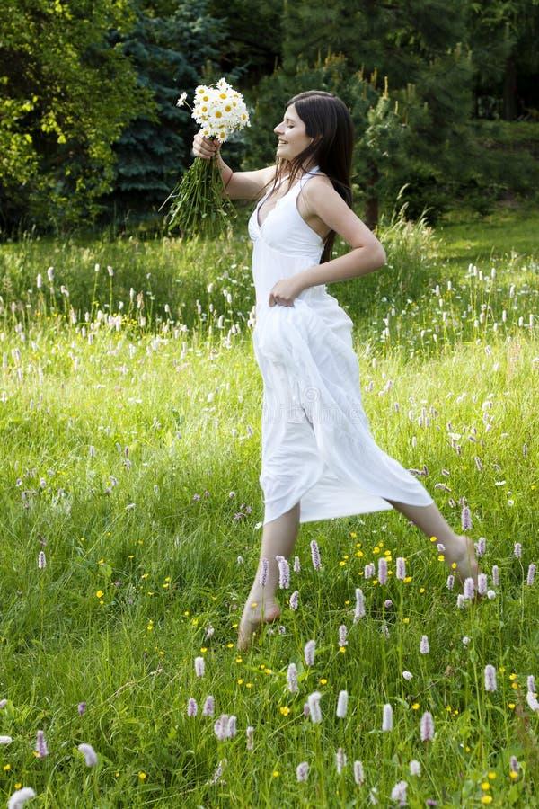 用花装饰的少年女孩华美的跳的草甸 免版税库存图片