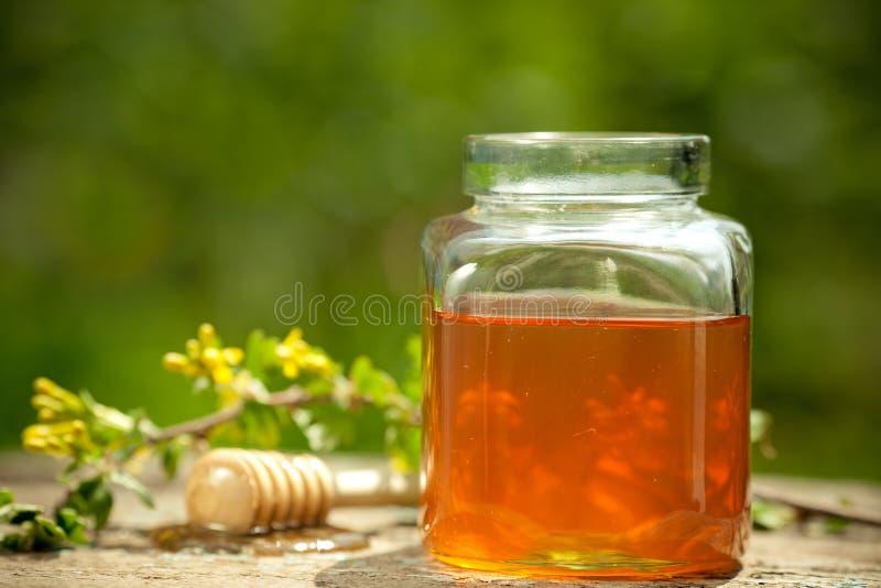 用花装饰的玻璃蜂蜜瓶子 库存图片