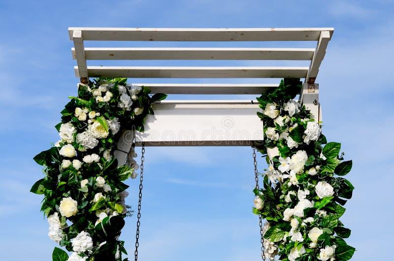 用花agains天空蔚蓝装饰的白色摇摆在海滨附近 免版税库存图片