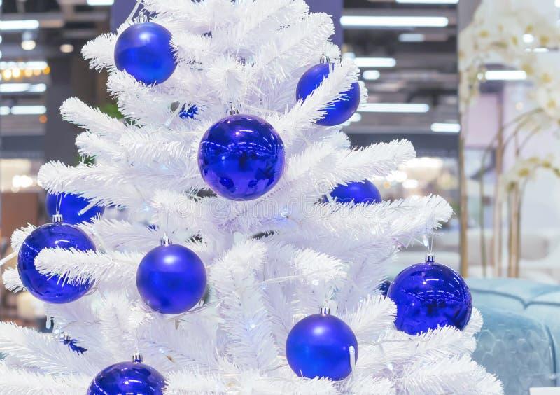 用蓝色球装饰的白色圣诞节快乐树 库存图片