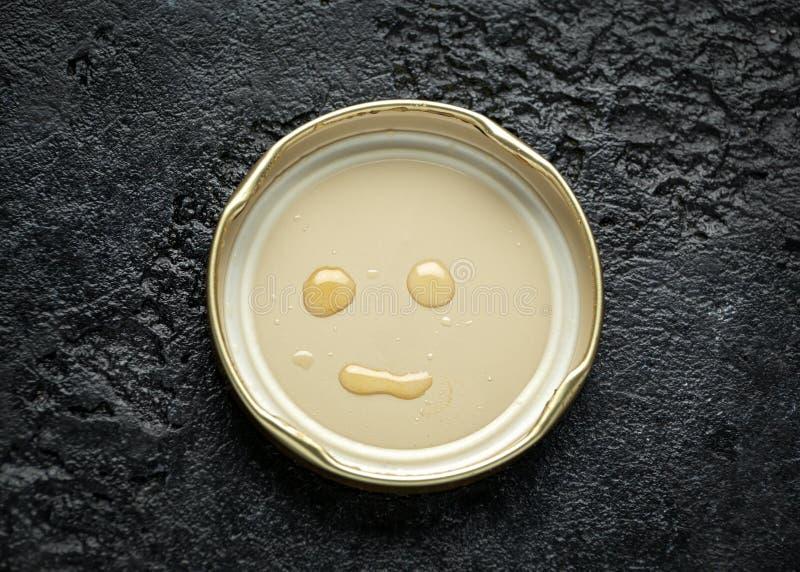 用蜂蜜下落做的面孔微笑在盒盖 库存图片