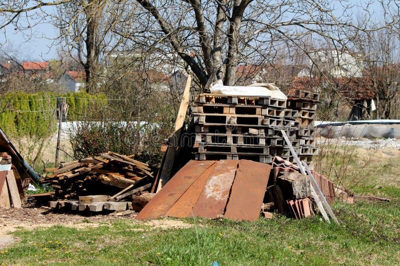 用被围拢的金属板报道的堆木板台和委员会和尼龙用未割减的草和高大的树木在背景中 免版税库存图片