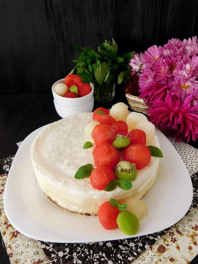 用西瓜、瓜和猕猴桃球形的片断装饰的白蛋糕 免版税库存图片