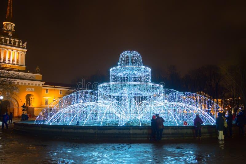 用诗歌选和圣诞灯装饰的有启发性喷泉,装饰元素在晚上 彼得斯堡俄国st 库存照片
