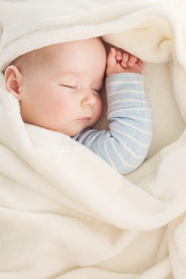 用软的白色毯子报道的婴孩睡觉 免版税库存照片