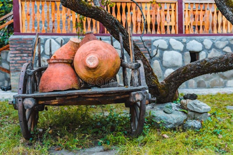 用酒的泥罐装载的推车在一个绿色庭院 免版税库存照片