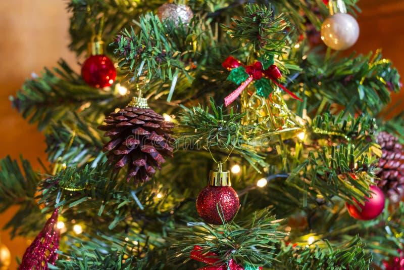用金铃、杉木锥体和五颜六色的球装饰的圣诞树 免版税图库摄影