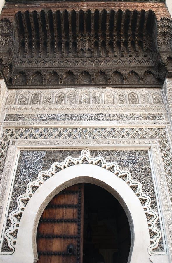 用阿拉伯马赛克和摩洛哥蔓藤花纹雕刻装饰的马蹄形拱在Fes Al巴厘岛中世纪麦地那  免版税图库摄影