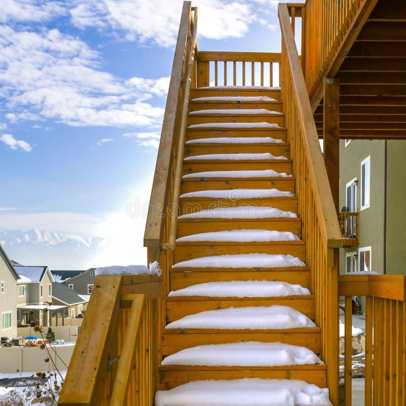 用雪报道的家的正方形室外木楼梯在冬天季节期间 免版税库存图片