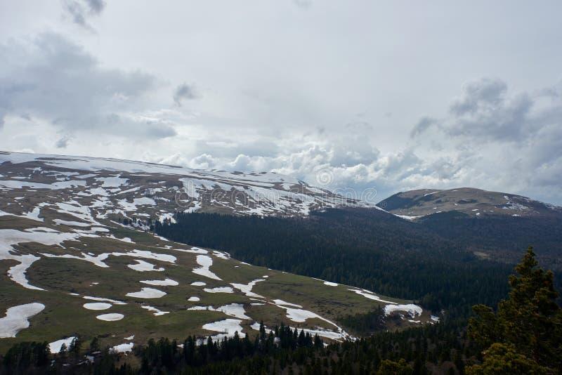 用雪报道的山高原在灰色天空下 库存图片