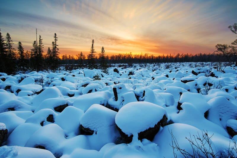 用雪报道的摇滚块领域和日落发光 免版税库存照片
