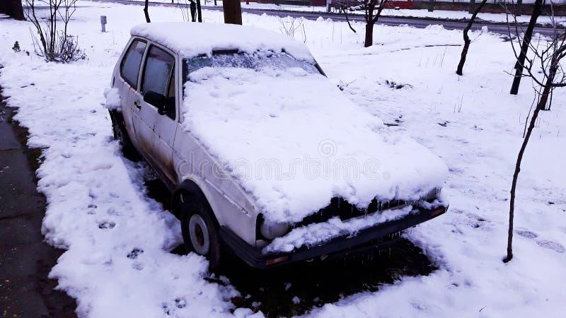 用雪盖的一辆老白色残破的汽车 免版税图库摄影