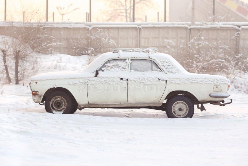 用雪盖的被放弃的汽车在冬天在日落,温暖的口气,侧视图 生锈,回收,处理的金属,写道 库存图片