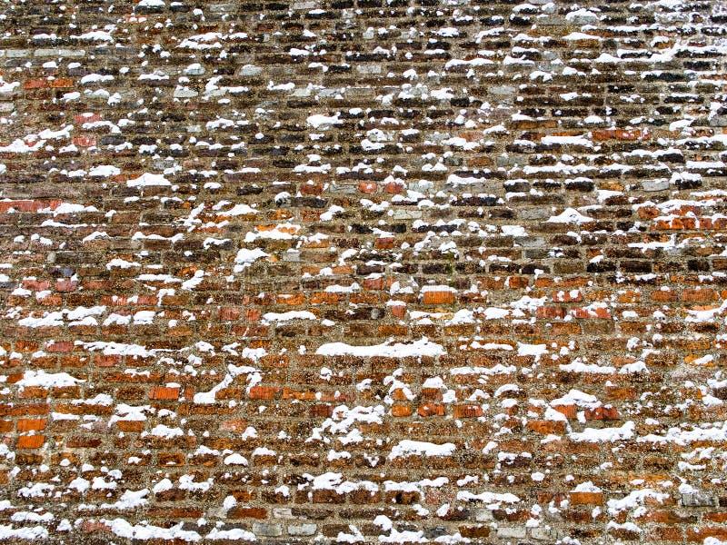 用雪花盖的宽红砖墙壁 免版税库存图片