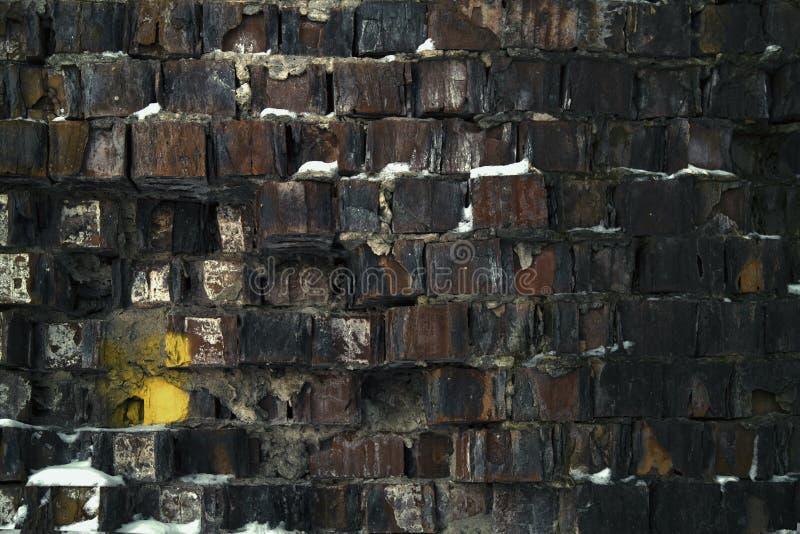 用雪部分地盖的老打破的砖墙 免版税库存照片