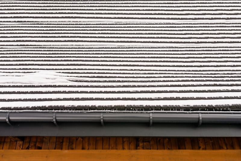 用雪,垂悬在天沟上的冰柱层数盖的一个木屋顶  大厦的一个可看见的木门面 免版税库存照片