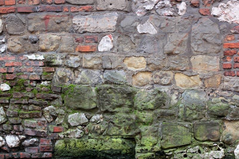 用青苔和大石头盖的老腐朽的墙壁砖克拉科夫,波兰 免版税库存图片