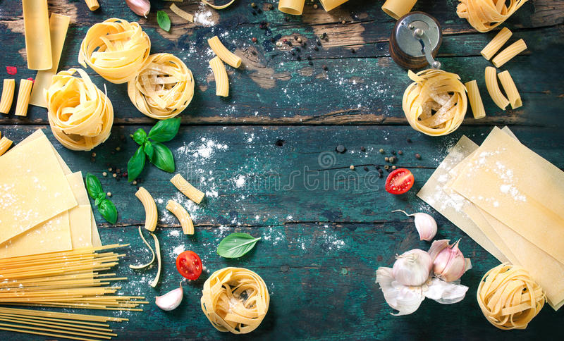 用面团、健康或者素食主义者概念的不同的类型的意大利食物背景 免版税图库摄影