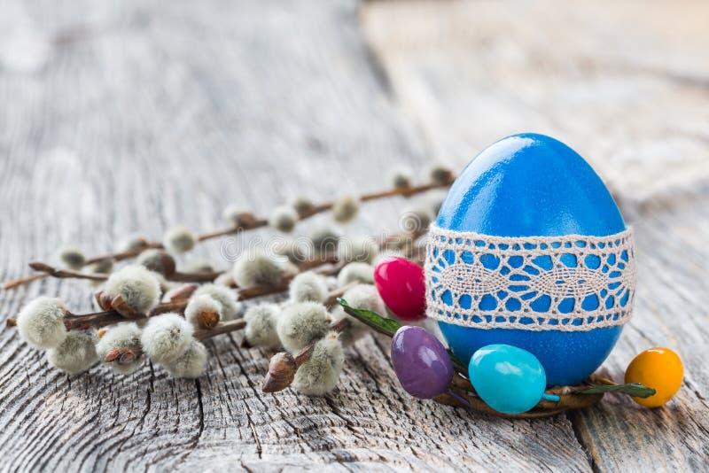 用鞋带装饰的蓝色复活节彩蛋和杨柳在木背景分支 选择聚焦 免版税库存照片