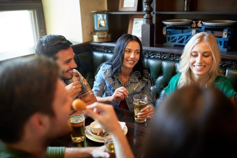 用餐和喝啤酒的朋友在餐馆 免版税库存图片
