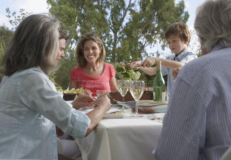 用餐在庭院里的三一代家庭 库存照片