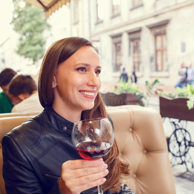 用餐在有杯的餐馆的女孩酒 免版税库存照片